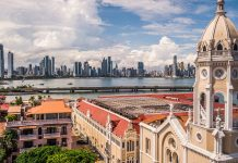 The Panama City skyline rises up in the distance behind a historic cathedral. Photo by Duarte Dellarole