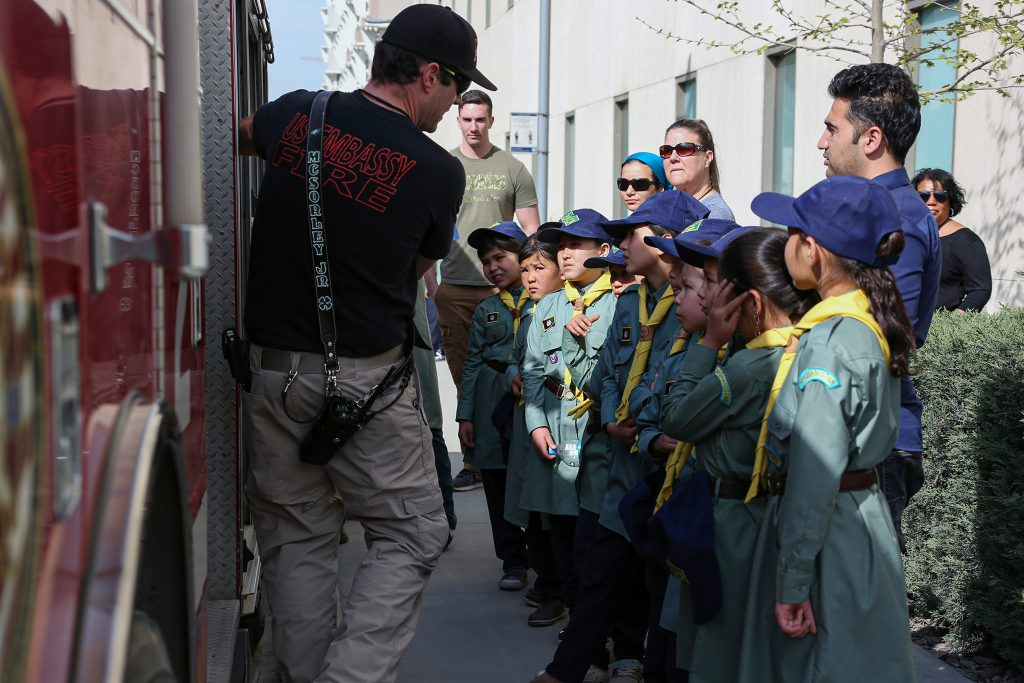 An Embassy Kabul firefighter explains the capabilities of their fire trucks to Afghan scouts, April 2019. Photo courtesy of Embassy Kabul