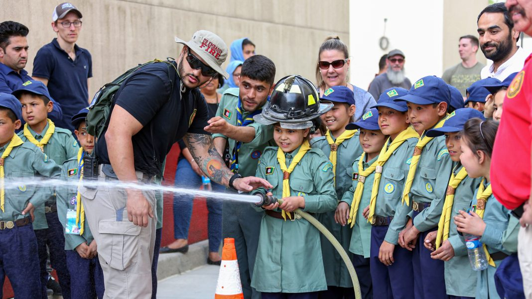 An Afghan girl scout is given fire hose training from an Embassy Kabul firefighter, April 2019. Photo courtesy of Embassy Kabul