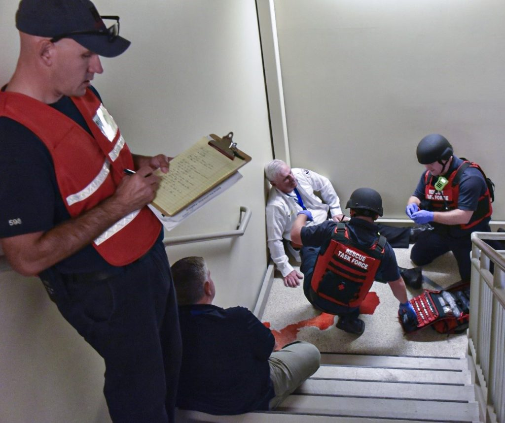 The Rescue Task Force treats an injured victim, while an evaluator assesses their response. Photo by Judy Emmert