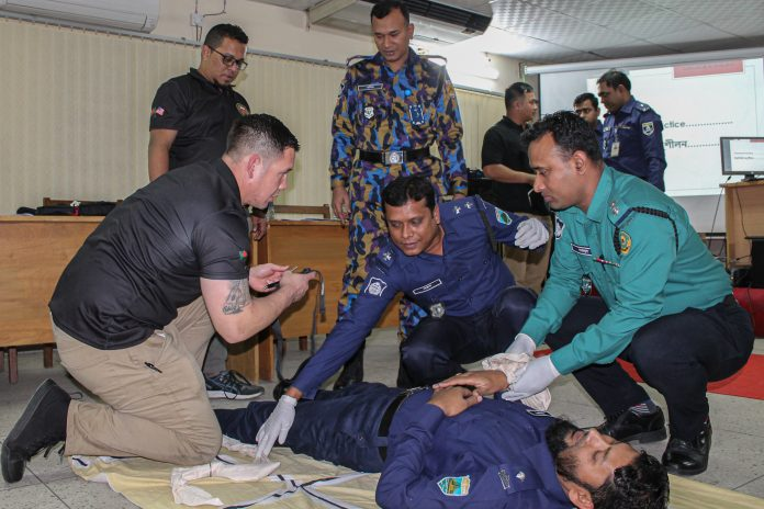 Staff Sergeant Christopher Liu (far left), who serves as a civil-military support element medical sergeant for Embassy Dhaka's U.S. Indo-Pacific Command Augmentation Team, demonstrates the proper application of a tourniquet during the Medical First Responder Seminar, Jan. 5, 2020. Photo by Mary Rosary Buchanan