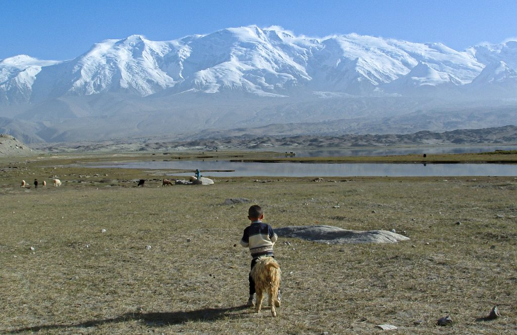 An ethnic Kyrgyz-Chinese boy with his nomadic family's sheep, is shown along the shore of Xinjiang's Karakul Lake in 2004. Photo by Beau Miller