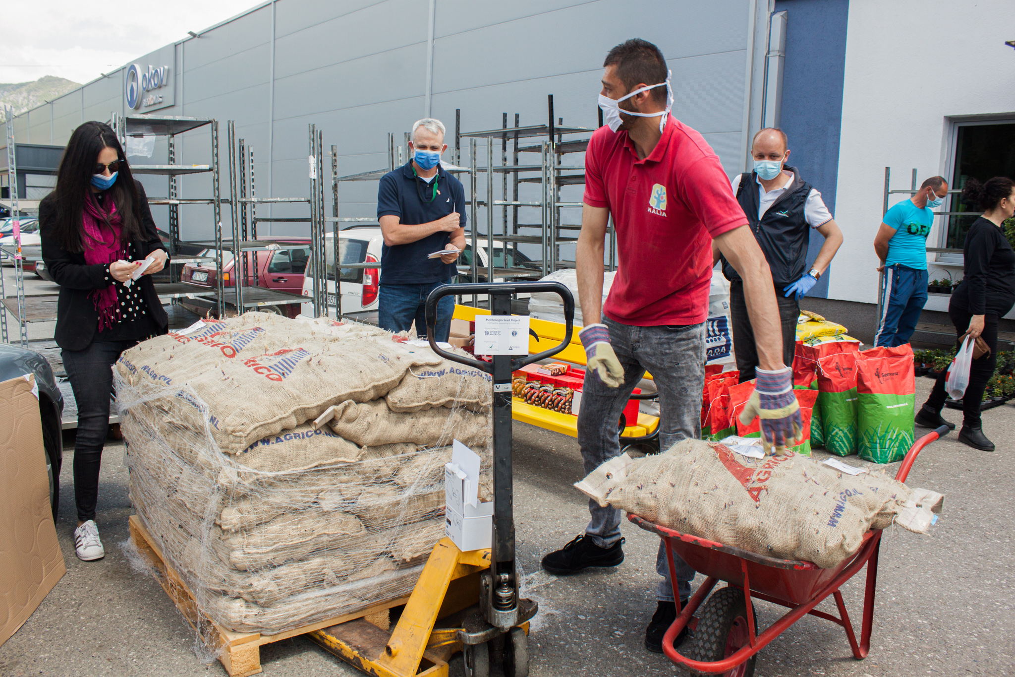 Lt. Col. Robert C. Perry (center, blue shirt) and Defense Attaché Office Coordinator Meri Perisić (left) receive seeds and potato slips being prepared for distribution in Berane, Montenegro. Photo courtesy of Jelena Krivčević