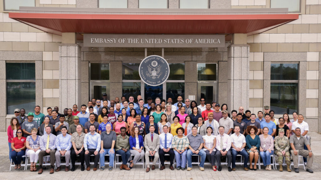 Embassy staff joins together in front of the embassy, 2020. The building, designed in 2004, is a well-known landmark in Belmopan—Belize's tiny capital. Photo courtesy of Mission Belize