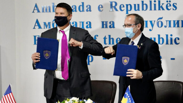 Under Secretary of State for Economic Growth, Energy, and the Environment Keith Krach and Prime Minister Avdullah Hoti bump elbows after signing Kosovo's memoranda of understanding on 5G security, Oct. 28. State Department photo
