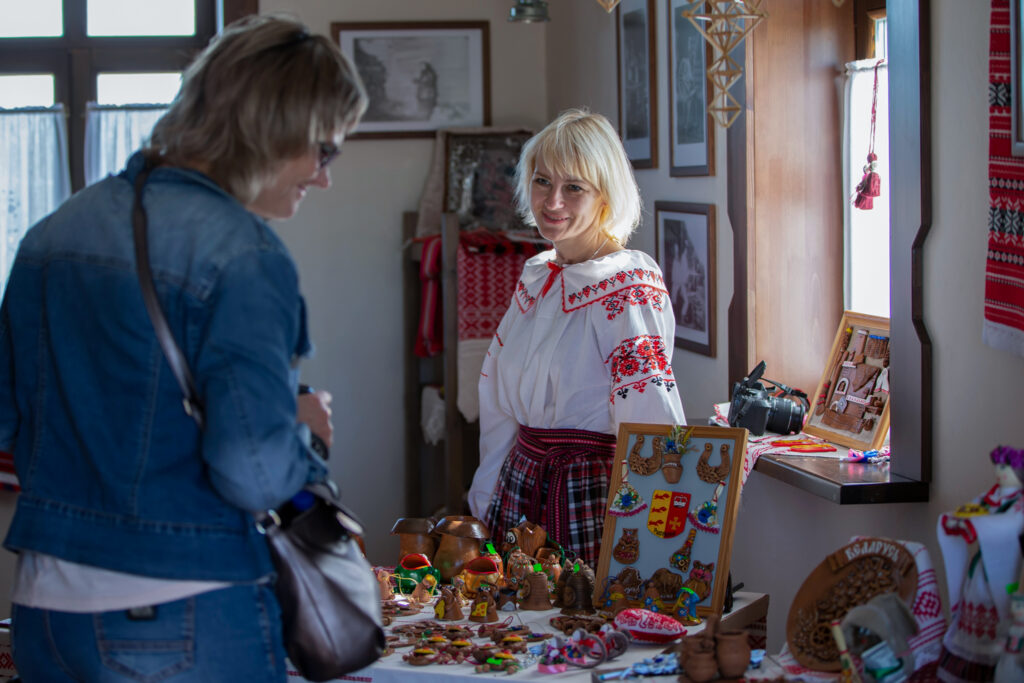 A shop owner markets souvenirs to a visitor in the village of Lyaskovichi, May 30, 2019. Photo by Svetlana Lazarenka