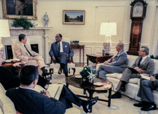 Former President Ronald Reagan talks with then-Ambassador to South Africa Edward J. Perkins at the White House, May 1987. Seated at right are Secretary of State George Shultz, U.S. National Security Adviser Frank Carlucci, and, at far right, National Security Council Senior Director for Africa Hank Cohen. Photo courtesy of the Foreign Service Journal
