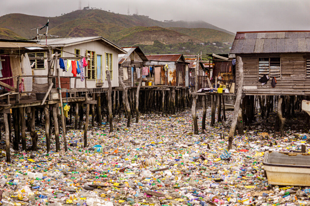 Plastic water bottles fill an entire body of water surrounding wooden villages off the coast of Port Moresby, creating an environmental catastrophe. Photo by The Road Provides
