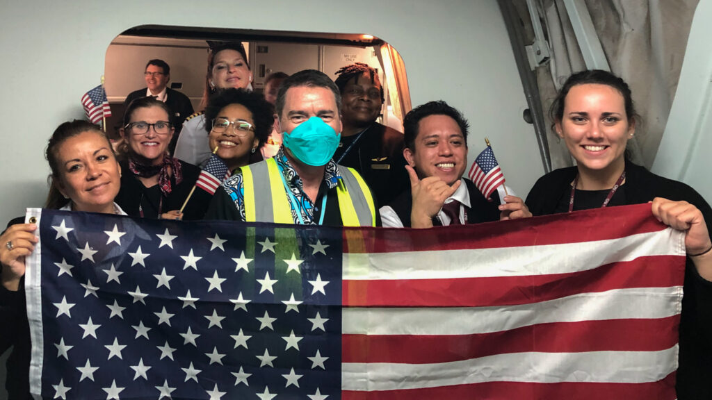 Embassy Port Moresby staff worked tirelessly to coordinate complicated logistics to evacuate more than 220 American citizens at the start of the COVID-19 pandemic in Papua New Guinea, April 2020. Public Affairs Officer Chad Morris stands masked among the Atlas Air charter crew. Photo by Patrick Neeley