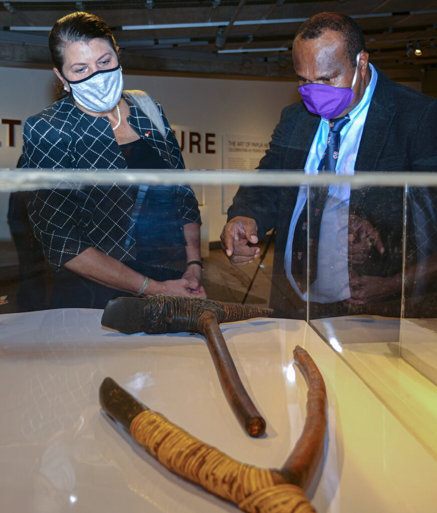 U.S. Ambassador to Papua New Guinea, Solomon Islands, and Vanuatu Erin McKee (left) formally handed over to the PNG National Museum and Gallery 133 cultural artifacts recovered from an illegal collection in the United States. Museum Director Dr. Andrew Motu (right) describes traditional handmade tools on display at the museum. Photo by Sophie Yaruso