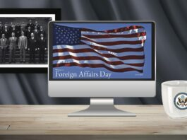 A photo of the second graduating class of the Foreign Service, 1925, hangs behind a computer screen showing the Foreign Affairs Day opening slide, with a Department of State mug placed on the desk.