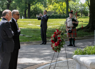 A musician plays Taps on his bugle while Ambassador Kenneth Merten (left) and Diplomatic and Consular Officers Retired (DACOR) President James Dandridge II (second from left) lay a wreath at the DACOR memorial monument, May 31. Photo by Jenifer Morris