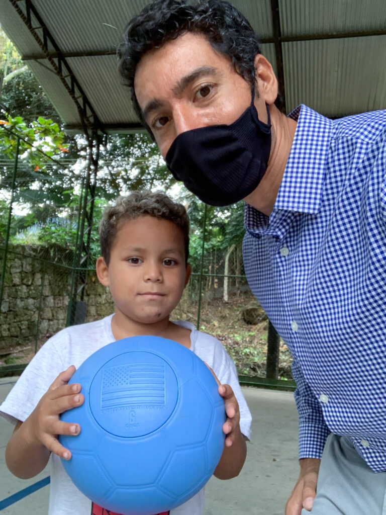 Six-year old Dainer Hernandez (left), a Venezuelan refugee, received a One World ball and coaching from Public Affairs Officer Paco Perez (right). Photo by Paco Perez