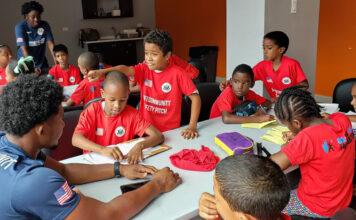 "SafeCommuniTT participants and mentors finish a homework assistance segment. Photo by Jonathan ""Jono"" Hirst."