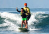 A surfing coach assists a student with disabilities in an adaptive surfing clinic organized by 2019 Global Sports Mentoring Program Sport for Community alumnus Daniel Gomez De la Vega in the state of Nayarit, Mexico, May 2021. Photo courtesy of Daniel Gomez De la Vega