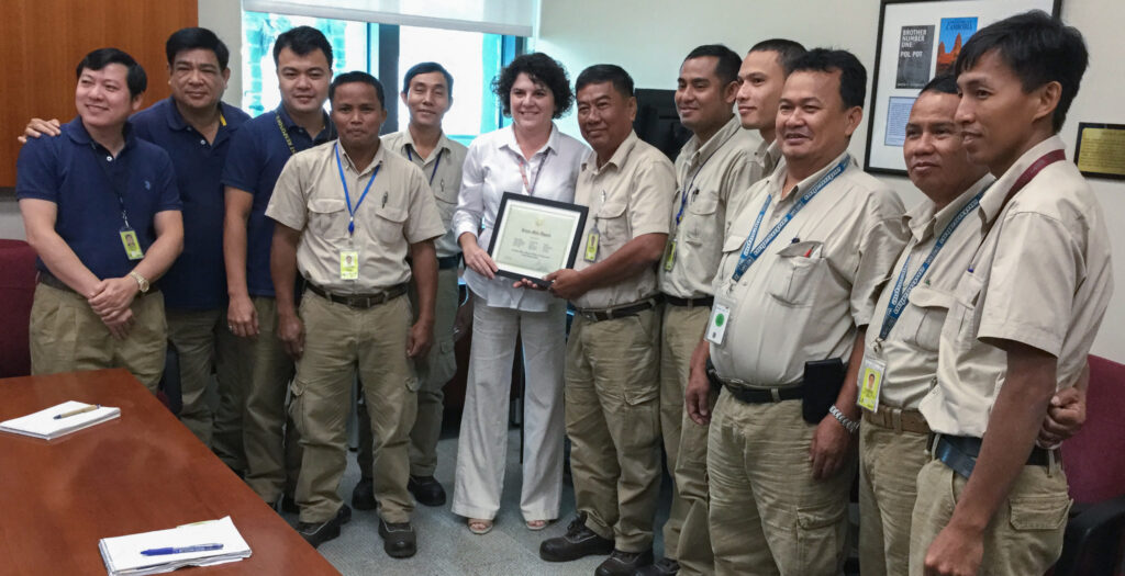 """Facility Manager Susan Meyerson (sixth from left) hands her staff at Embassy Cambodia the """"Extra Mile Award"""" for their exceptional work at post. Meyerson has served as a facility manager for the Department of State for 10 years. Photo courtesy of the Bureau of Overseas Buildings Operations"""
